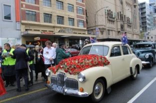 Photo No. 1 of 12 - Anzac Day March at Federation Square, Melbourne, Australia featuring Australia's first own car – its hood here blanketed with a sheath of poppies photo taken by Karen Robinson 25.4.2015.JPG