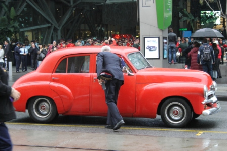 Photo No. 12 of 12 - Anzac Day March at Federation Square, Melbourne, Australia featuring Australia's first own car – its hood here blanketed with a sheath of poppies photo taken by Karen Robinson 25.4.2015.JPG