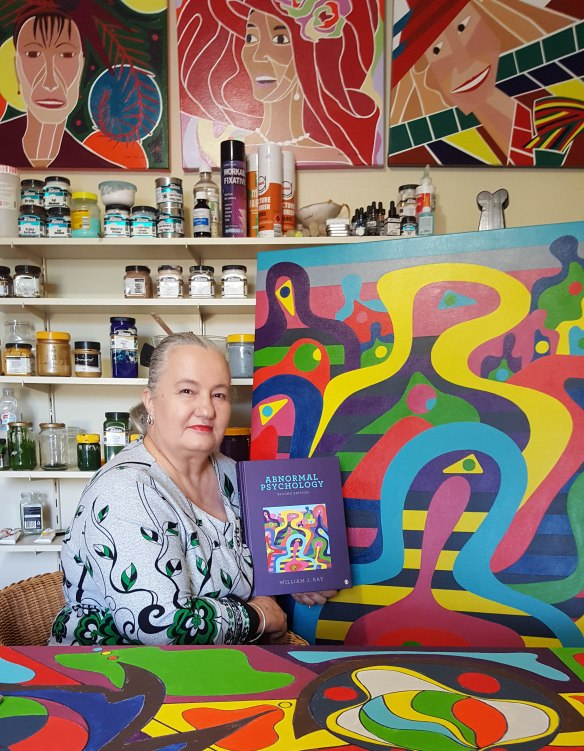 Karen Robinson at Home Art Studio holding book titled 'Abnormal Psychology' featuring on the front cover her original painting titled 'For Ones' Well-being' March 2017 www.idoartkarenrobinson.com NB: All images are copyright protected
