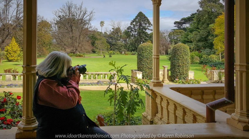 "Elsternwick, Victoria - Australia_Photographed by ©Karen Robinson_ www.idoartkarenrobinson.com September 10, 2017 Comments: My hubby and I with the Craigieburn Camera Club at Rippon Lea House and Gardens. ""It is one of Australia's finest grand suburban estates and the first to achieve National Heritage Listing, recognising its unique significance. The historic mansion is located within a vast pleasure garden of sweeping lawns that cover more than 14 acres and features a windmill, lookout tower, heritage orchard, lake, waterfall, fernery and more!"" Photograph featuring Karen taking photos across the sweeping lawns from the Mansion's balcony."