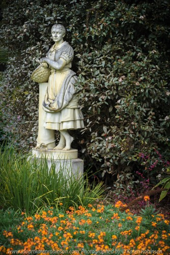 """Elsternwick, Victoria - Australia_Photographed by ©Karen Robinson_ www.idoartkarenrobinson.com_September 10, 2017 Comments: My hubby and I with the Craigieburn Camera Club at Rippon Lea House and Gardens. """"It is one of Australia's finest grand suburban estates and the first to achieve National Heritage Listing, recognising its unique significance. The historic mansion is located within a vast pleasure garden of sweeping lawns that cover more than 14 acres and features a windmill, lookout tower, heritage orchard, lake, waterfall, fernery and more!"""" Photograph featuring garden statue 'lady holding basket' standing amongst flowering bulbs."""
