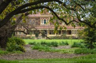 """Elsternwick, Victoria - Australia_Photographed by ©Karen Robinson_ www.idoartkarenrobinson.com_September 10, 2017 Comments: My hubby and I with the Craigieburn Camera Club at Rippon Lea House and Gardens. """"It is one of Australia's finest grand suburban estates and the first to achieve National Heritage Listing, recognising its unique significance. The historic mansion is located within a vast pleasure garden of sweeping lawns that cover more than 14 acres and features a windmill, lookout tower, heritage orchard, lake, waterfall, fernery and more!"""" Photograph featuring front view of Mansion."""
