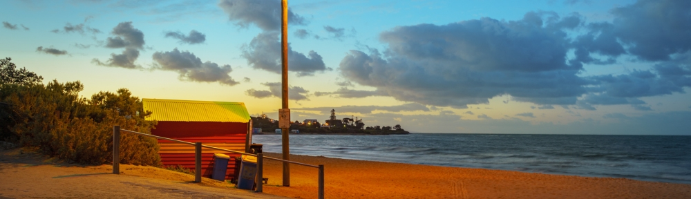 Brighton, Victoria - Australia 'Sunrise at Brighton Beach' Photographed by ©Karen Robinson Dec 2020 Comments: Early morning at Brighton Beach capturing beautiful sunrise lighting along the shore light and looking out over Port Phillip Bay. Photograph featuring single Brighton Beach Bathing Box bathed in warm street lighting
