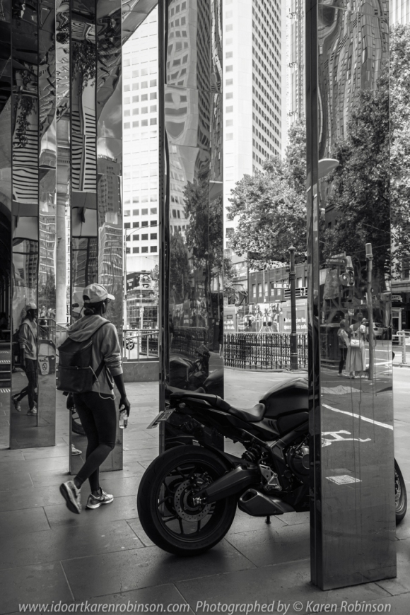 Melbourne, Victoria - Australia 'Little Bourke Street' Photographed by Karen Robinson Jan 2021 Comments: Decided to venture into the City of Melbourne - Chinatown on Little Bourke Street to do some Street/Documentary Style Photography. Photograph featuring a parked motorbike on the corner of Elizabeth Street and Little Bourke Street. Tall mirror columns reflected images of the bike and people walking through the area.