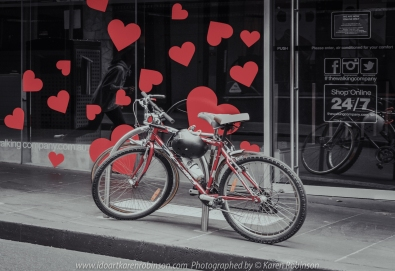 Melbourne, Victoria - Australia 'Little Bourke Street' Photographed by Karen Robinson Jan 2021 Comments: Decided to venture into the City of Melbourne - on Little Bourke Street to do some Street/Documentary Style Photography. Photograph featuring push bikes leaning on the bike stand with red hearts on shop window behind.