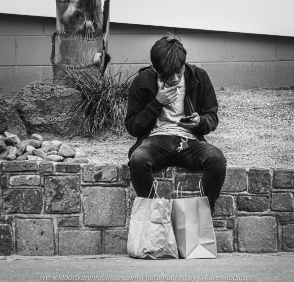 Williamstown, Victoria - Australia 'Williamstown Newport Foreshore' Photographed by Karen Robinson February 2021 Comments: Hunt and Shoot day with Craigieburn Camera Club looking for interesting subjects to photograph. Photograph featuring young man stopping to have a smoke and check his phone messages after doing some shopping.